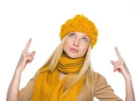 Woman in hat and scarf pointing up on copy space photo