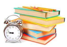 reloj despertador y libros multicolores.