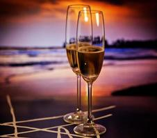 Champagne glasses on tropical beach at sunset