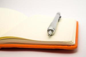 Blank notebook and pencil isolated on white background photo
