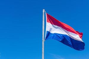 Dutch flag against blue sky photo