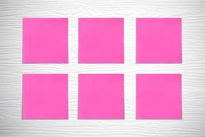 Pink note pads on white wooden wall photo