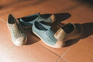 Plastic shoes on tile background with copy space