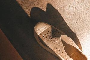 Zapatos de plástico sobre fondo de azulejos con espacio de copia foto