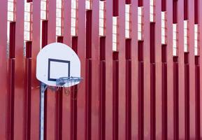 Basketball hoop on red metallic wall structure