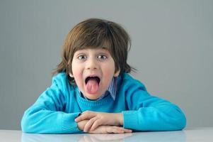 smart beautiful kid doing silly face isolated on grey photo