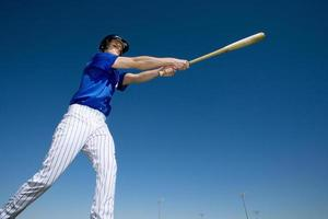Baseball batter, in blue uniform, hitting ball during competitiv