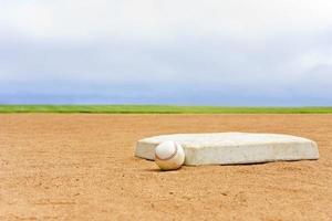 Baseball field base and ball, blue sky background
