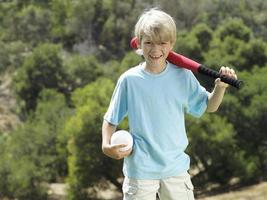 Blonde boy standing in park with softball bat and ball photo