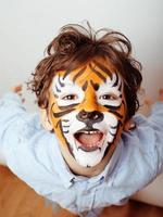 little cute boy with faceart on birthday party close up photo