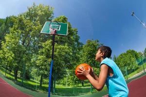 Arabische jongen klaar om bal in basketbal doel te gooien