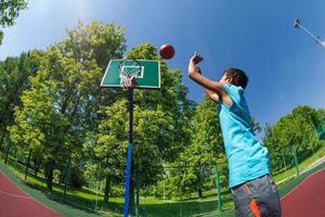 Arabische jongen gooit bal in basketbal doel