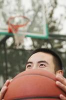 jeune homme, couvrant son visage, à, basket-ball