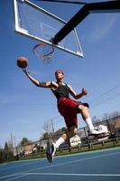 Man playing basketball on an outdoor court in mid jump