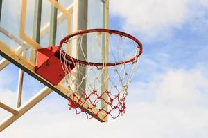 Basketball hoop with cage with blue sky background
