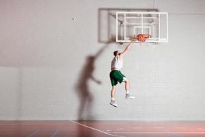 Tough healthy young man playing basketball in gym indoor. photo