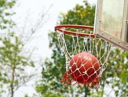 Basketball falls through hoop photo