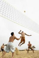 Male Friends Playing Volleyball On Beach photo