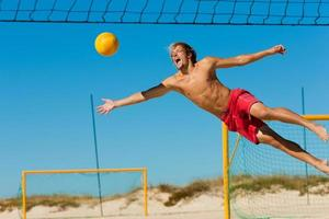 Man at beach leaping in air as he tries to get volleyball