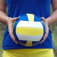 Girl holding a colorful sports ball for volleyball. Closeup Photo