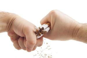 manos humanas rompiendo violentamente cigarrillos foto