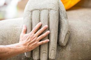 Human hand and hand of buddha statue