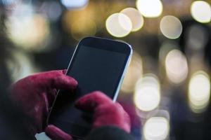 manos humanas con teléfono inteligente en la ciudad por la noche foto