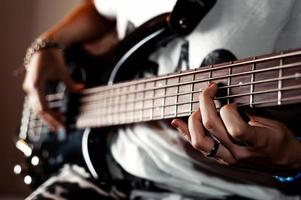 Human hand taken chord on electric bass guitar fingerboard closeup