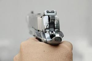 Human hand holding gun, hand aiming a handgun, .45 pistol.
