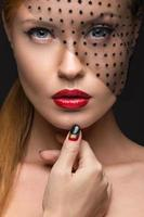 Beautiful girl with a veil, evening makeup, black and red