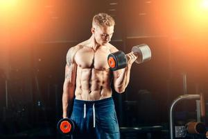 Athlete muscular bodybuilder training back with dumbbell  in the gym