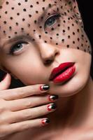 Beautiful girl with a veil, evening makeup, black and red photo