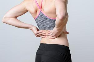 Close up Athletic Woman Holding her Injured Back photo