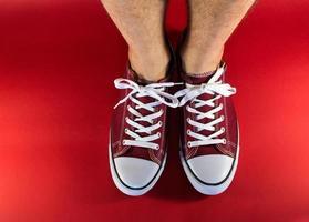 treinadores de lona vermelha e pés humanos