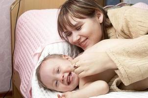 la madre juega con el niño foto