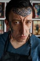 Closeup retrato del maestro del tatuaje en estudio