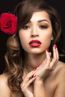 Beautiful girl with red lips and rose in her hair.