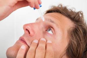 Young Man Putting Eye Drops photo