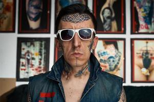 artista del tatuaje en chaleco vaquero y gafas de sol
