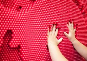 Baby hands making handprint on the red pin toy