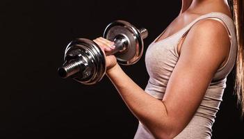 athletic woman working with heavy dumbbells photo