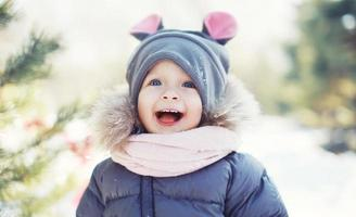 Funny baby laughing outdoors in winter day