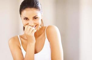 Imagen de mujer joven cubriendo su boca mientras se ríe