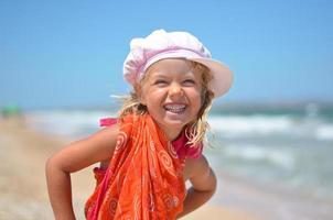 retrato de menina feliz em vestido laranja na praia