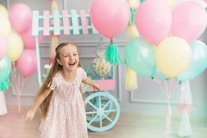 Niña se ríe en un estudio decorado con muchos globos foto
