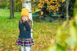 Girl playing hide and seek near tree in autumn park photo
