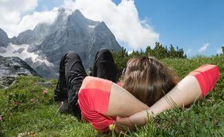 mujer joven relajante en un prado de montaña