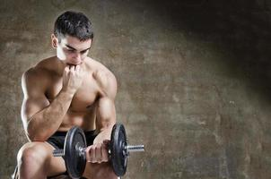 thoughtful and relaxed man training with dumbbell photo