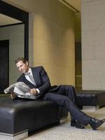 Empresario relajado leyendo el periódico en el vestíbulo de la oficina foto