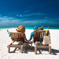 Couple relax on a beach at Maldives photo